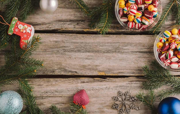 Christmas background with baubles and spruce tree branches on a wooden surface