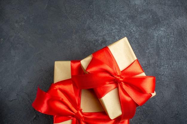 Sfondo di natale con bellissimi doni con nastro a forma di fiocco su uno sfondo scuro
