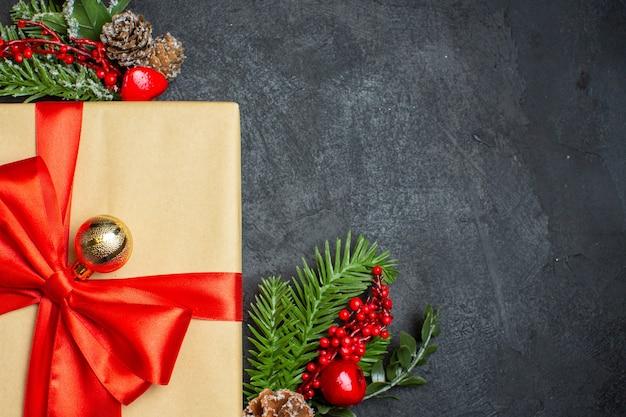 Sfondo di natale con bellissimi regali con nastro a forma di arco e accessori per la decorazione di rami di abete su una foto a metà colpo di tavolo scuro
