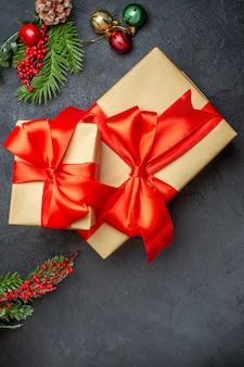 Sfondo di natale con bellissimi doni con nastro a forma di fiocco e accessori per la decorazione di rami di abete su una vista verticale del tavolo scuro