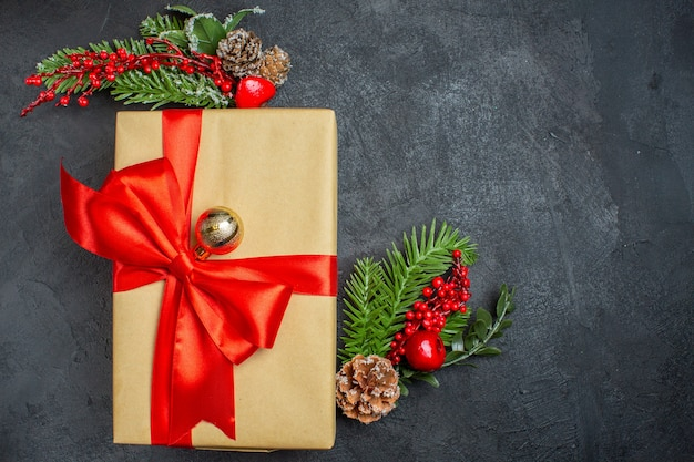 Sfondo di natale con bellissimi regali con fiocco a forma di fiocco e accessori per la decorazione di rami di abete sul lato destro su un tavolo scuro