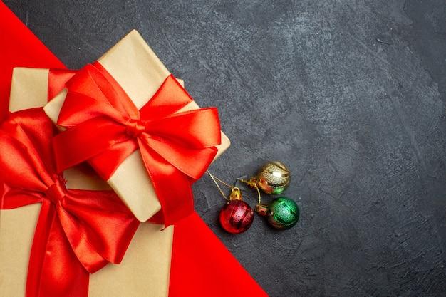 Sfondo di natale con bellissimi doni con nastro a forma di fiocco su un asciugamano rosso e accessori di decorazione su uno sfondo scuro