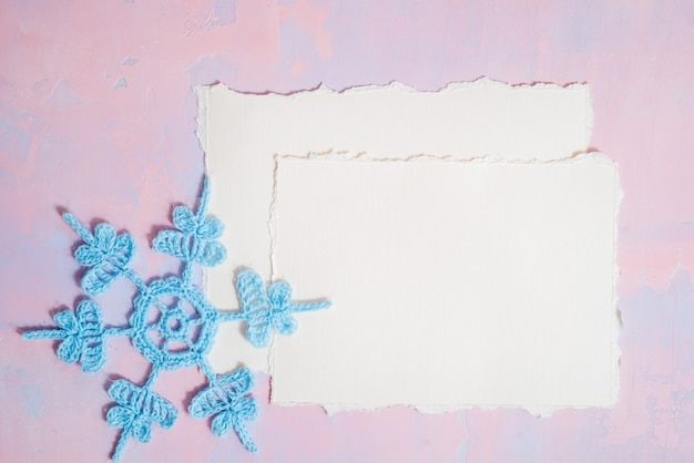 Christmas background with blank notebook, blue crocheted snowflake, handmade on a purple-pink background.  torn paper trend. flat lay, top view. copyspace.