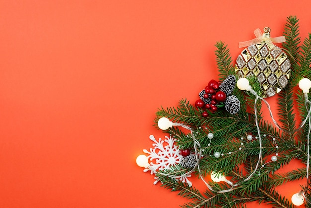 Christmas background with branches and decorations on a red table.