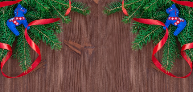 Christmas background with branches of fir and decorations on a brown wooden background