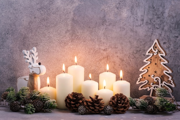 燃えるろうそくと円錐形の木とクリスマスの背景