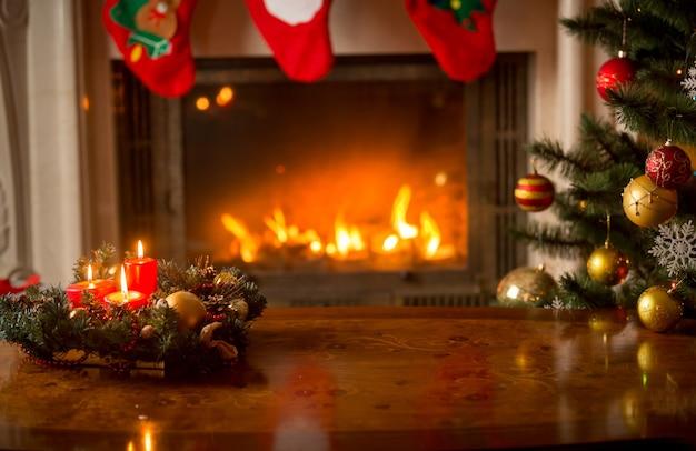 暖炉とクリスマスツリーの前に木製のテーブルの上のろうそくを燃やしてクリスマスの背景