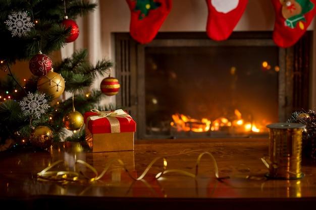 燃える暖炉、クリスマスツリー、ギフトボックス、テーブルとクリスマスの背景