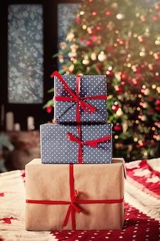 Рождественский фон с рождественскими подарками и рождественской елкой дома на рождество или новогоднюю открытку