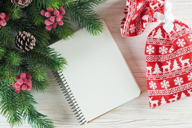 Новогодний фон с елкой и пустой запиской поздравительной открытки на белой деревянной поверхности.