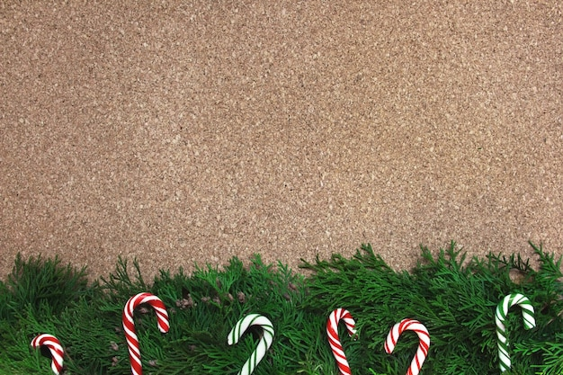 Christmas background with conifer branches and candy canes on a cork board