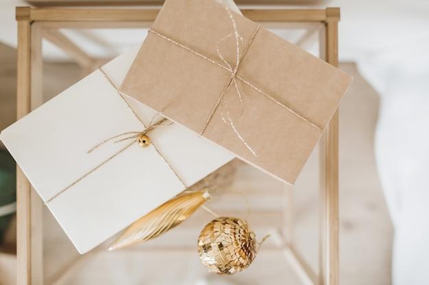 クラフトギフトボックスとゴールデンクリスマスボールのあるクリスマスの背景。フラットレイ