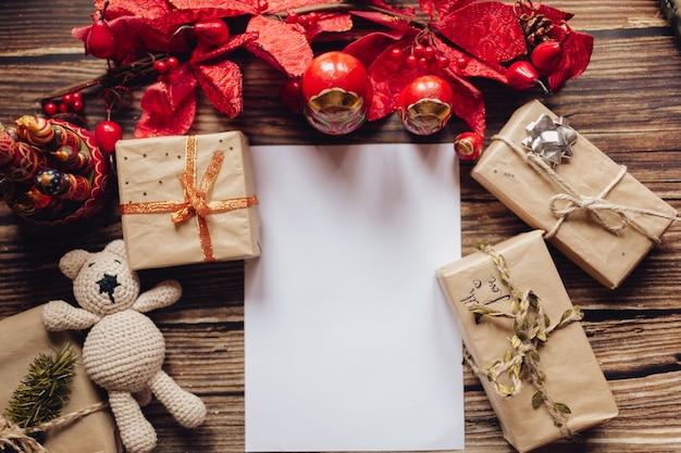 クラフト紙、ギフトボックス、手作りのクリスマスのおもちゃとクリスマスの背景。木製の机の上面図。飾りとクリスマスプレゼント。サンタクロースの手紙。