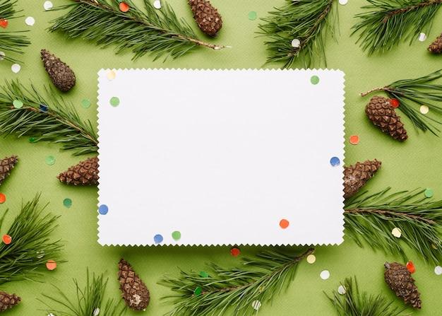 松の枝とお祝いの紙吹雪の装飾とクリスマスの背景。クリスマスクリープのコピースペースのある白いシート