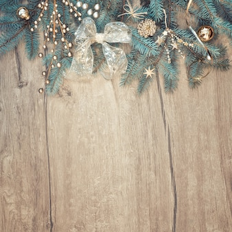 Christmas background with decorated fir tree branch border on wood