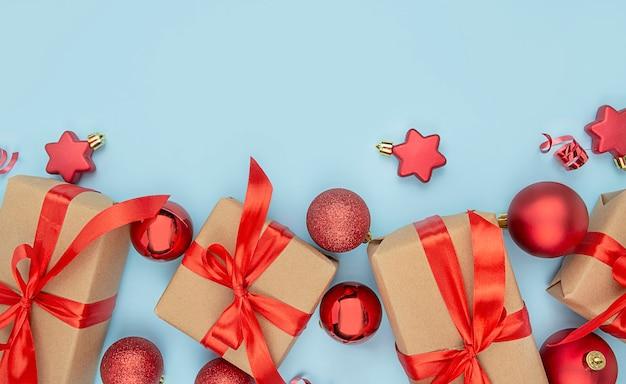 밝은 파란색 배경에 장식과 선물 상자가 있는 크리스마스 배경. 빨간 리본과 크리스마스 장식이 있는 종이 선물 상자. 공간의 복사본입니다.