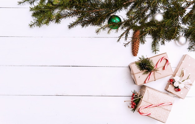 Новогодний фон с украшениями и подарочные коробки на деревянной доске