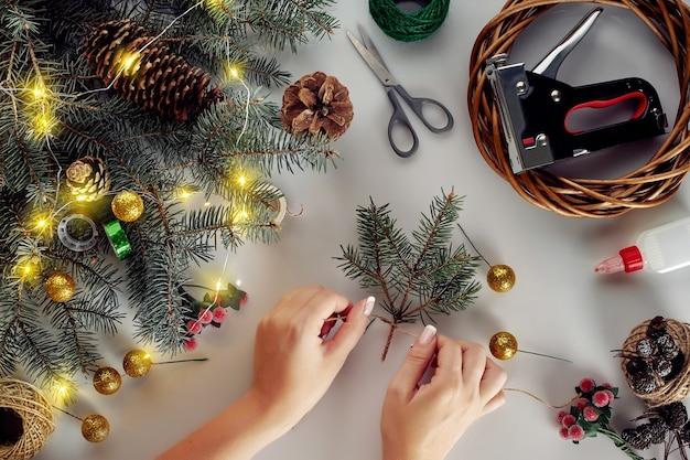 装飾、花輪、松ぼっくりのクリスマスの背景。白い背景の上のクリスマスツリーの枝で作られた花輪を作成します。