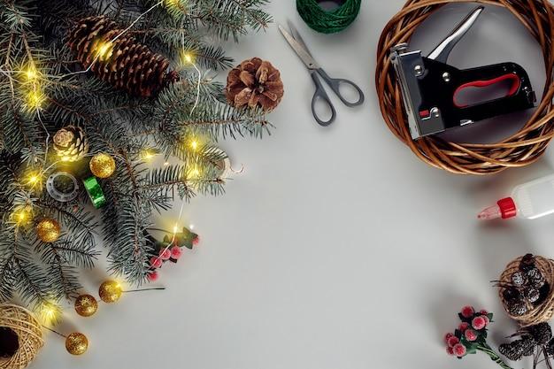 Новогодний фон с украшениями гирлянда и сосновые шишки, создающие венок из елки ...
