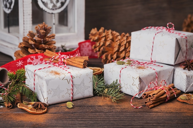 Christmas background with decorations and gift boxes on dark wooden board.
