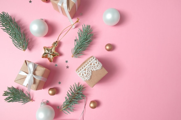 Christmas background with decorations and gift boxes on pink background