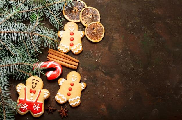 Новогодний фон с украшениями: пряники и свежие еловые ветки на темном фоне, вид сверху