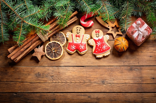Новогодний фон с украшениями: пряники и свежие еловые ветки на деревянном фоне, вид сверху