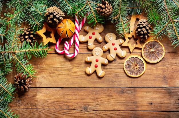 Новогодний фон с украшениями, пряники и свежие еловые ветки