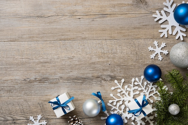 Christmas background with decorations and white gift boxes with blue ribbon on wooden table.
