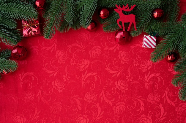 Christmas background with decorations and wide arch shaped leaf frame on red