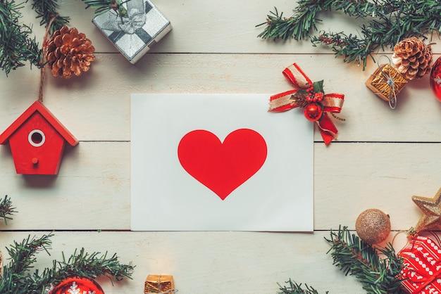 木製の背景にグリーティングカードの装飾とクリスマスの背景。コピースペースのある上面図