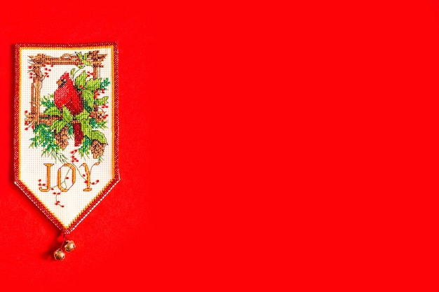Christmas background with decorative embroidered pennant on red background