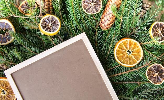 緑のとげのあるモミの木の枝にドライオレンジスライスと空のフレームボードとクリスマスの背景。お祝いの新年のデザイン要素。