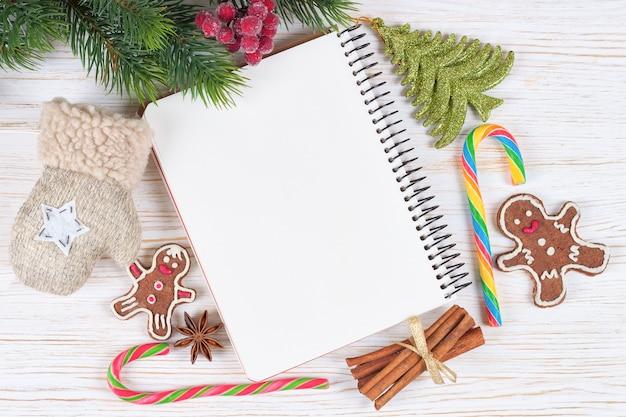 Новогодний фон с пустой запиской на белой деревянной поверхности.