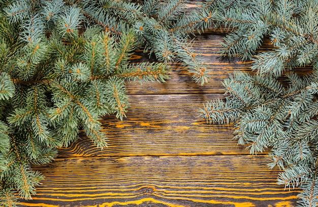 茶色の素朴な木製のテーブルにお祝いのアレンジメントとして配置された常緑の松の枝、コピースペースと高角度のクローズアップとクリスマスの背景