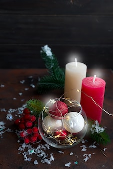 Christmas background with festive decoration, candles, light and balls in jar.