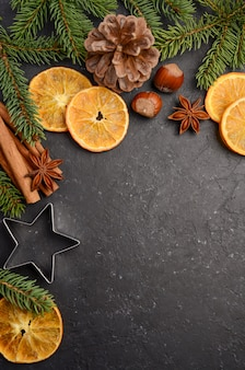 Christmas background with fir branches, cones, nuts and slices of dried orange.