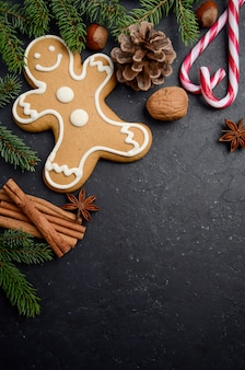 Christmas background with fir branches, cones, spices and gingerbread.