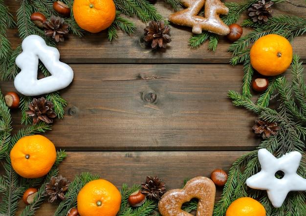 モミの枝、コーン、みかん、ナッツ、ジンジャーブレッドのクリスマスの背景
