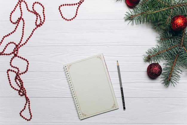 Рождественские фон с елки филиалов, украшения, подарочной коробке и пустой блокнот. пространство для текста. вид сверху.