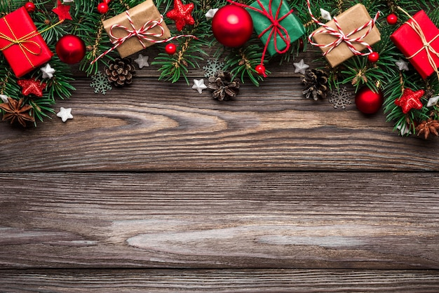 Christmas background with fir branches, decorations, gift boxes and pine cones on wooden table