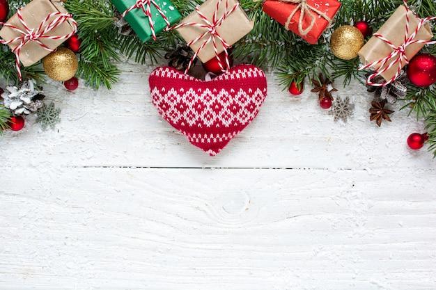 Новогодний фон с еловыми ветками, вязанным сердцем, украшениями, подарочными коробками и сосновыми шишками