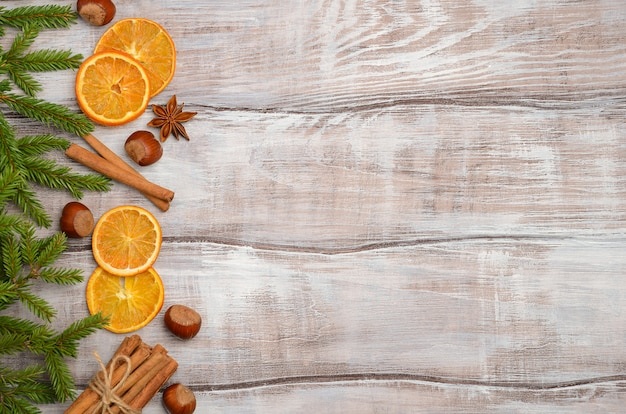 Christmas background with fir branches, nuts, spices and dried oranges.
