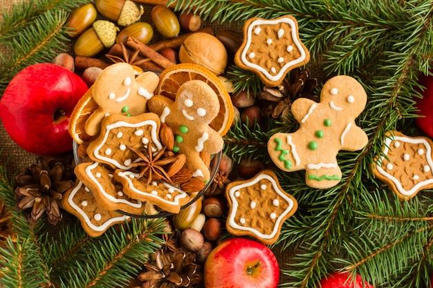 전나무 가지, 솔방울, 크리스마스 쿠키, 계피 스틱, 아니스 별이 있는 크리스마스 배경. 평면도.