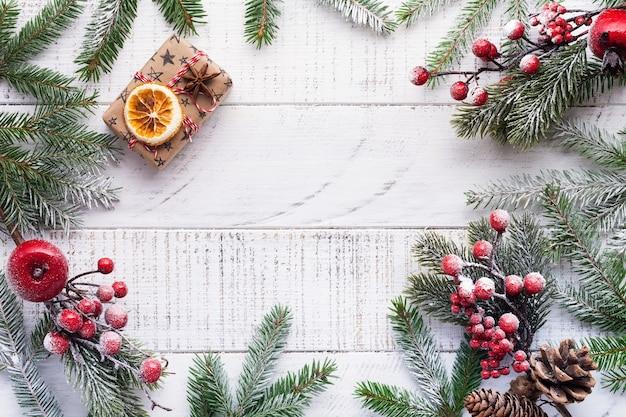전나무 가지, 솔방울, 선물 상자, 말린 오렌지, 스타 아니 스와 오래 된 흰색 나무 보드에 딸기 크리스마스 배경. 평면도.