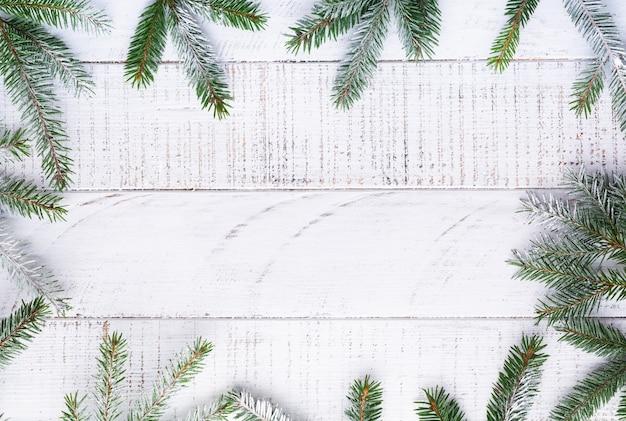 Новогодний фон с еловыми ветками, шишками, подарочной коробкой, сушеными апельсинами, звездчатым анисом и ягодами на старой белой деревянной доске. вид сверху.