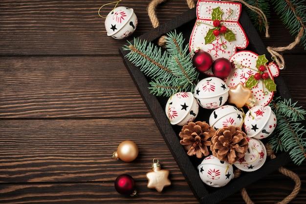 Новогодний фон с еловыми ветками, игрушками и колоколами на деревянном старом фоновом столе. выборочный фокус. вид сверху с копией пространства.