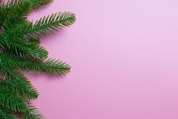 Новогодний фон с еловыми или сосновыми ветками на розовом фоне