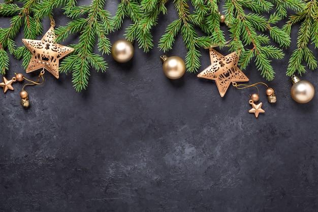 전나무 나무와 황금 공 및 어두운 돌 배경에 별 크리스마스 배경. 상위 뷰 복사 공간 - 이미지