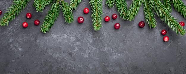 暗い石のテーブルにモミの木と赤いクランベリーとクリスマスの背景
